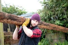 Le bûcheron masculin beau porte l'ouverture en bois son épaule images stock