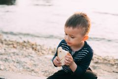 Le b?b? gar?on sur le fond de la mer au coucher du soleil mangeant un morceau de pain a grill? photographie stock libre de droits