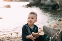 Le b?b? gar?on sur le fond de la mer au coucher du soleil mangeant un morceau de pain a grill? photo stock