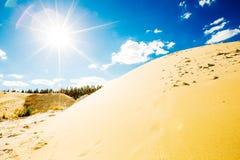 Le bac à sable s'est allumé par le soleil lumineux de midi sur le ciel bleu Photos libres de droits