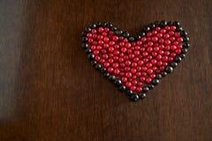 Le bacche del ribes nel telaio delle bacche del ribes nero sono presentate sotto forma di cuore su un fondo scuro di legno immagini stock libere da diritti