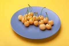 Le bacche ingialliscono la ciliegia sul piatto blu su fondo giallo, buon concetto di prodotto Fotografia Stock Libera da Diritti