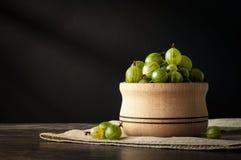 Le bacche mature succose di un'uva spina in un piccolo vaso di legno sul nero sorgono Raccolto dell'uva spina Immagini Stock