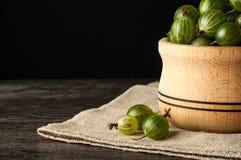 Le bacche mature succose di un'uva spina in un piccolo vaso di legno sul nero sorgono Raccolto dell'uva spina Fotografie Stock