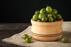Le bacche mature succose di un'uva spina in un piccolo vaso di legno sul nero sorgono Raccolto dell'uva spina Fotografia Stock
