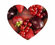 Le bacche nel cuore modellano isolato su un bianco Bacche assortite di forma del cuore su fondo bianco Ribes rosso maturo, fragol Immagine Stock