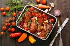Le bacchette di pollo crude hanno preparato per la torrefazione in una pentola fotografia stock