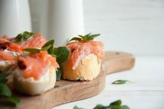 Le baguette con formaggio cremoso, salmone, hanno asciugato i pomodori ed il basilico Immagini Stock Libere da Diritti