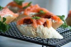 Le baguette con formaggio cremoso, salmone, hanno asciugato i pomodori ed il basilico Fotografia Stock