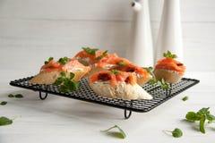Le baguette con formaggio cremoso, salmone, hanno asciugato i pomodori ed il basilico Immagini Stock