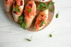 Le baguette con formaggio cremoso, salmone, hanno asciugato i pomodori ed il basilico Fotografie Stock