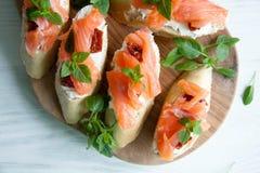 Le baguette con formaggio cremoso, salmone, hanno asciugato i pomodori ed il basilico Immagine Stock