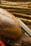 Le baguette del pane francese hanno tagliato sul bordo di legno con il coltello con un cho fotografia stock