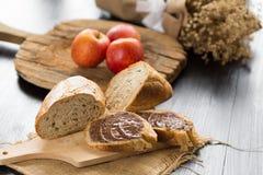 Le baguette del pane francese hanno tagliato sul bordo di legno con il coltello con un cho immagini stock libere da diritti