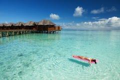 Le bain de femme et détendent sur le matelas gonflable en mer photos libres de droits