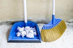 Le balai et la pelle à poussière bleus pour la maison fonctionnent avec des papiers de déchets sur le flo Images libres de droits