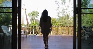 Le balcon ouvert de fille sortent à la terrasse étirant des bras de retour vue arrière, vue de matin de forêt tropicale banque de vidéos