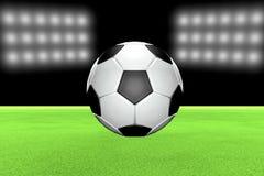 Le ballon de football au-dessus du champ avec le stade s'allume sur le dos Photographie stock libre de droits