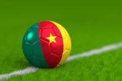 Le ballon de football avec le drapeau canerounais 3D rendent Images stock