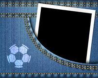 Le ballon de football sur des jeans et le cadre vide de photo dans des blues-jean empochent Photographie stock