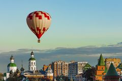 Le ballon rouge et blanc vole très bas au-dessus de la ville, directement au-dessus de Christian Church et du ciel sans nuages de Image stock
