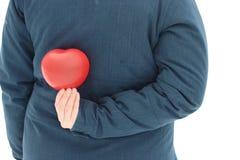 Le ballon rouge sous forme d'homme de coeur se tient dans des ses mains cadeau une Saint-Valentin givrée de jour le 14 février -  photographie stock