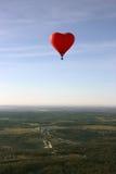 Le ballon rouge sous forme de coeur rouge plane au-dessus du terrain Image stock