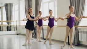 Le bambine adorabili in tute luminose stanno avendo lezione di balletto classico che imparano i movimenti della gamba con l'inseg stock footage