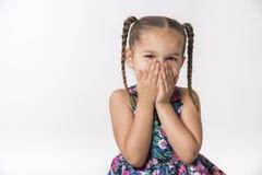 Le bambine copre la bocca di mani fotografia stock