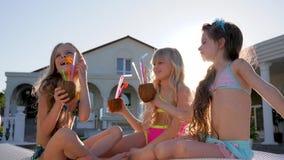 Le bambine in costume da bagno si divertono vicino alla villa in lampadina, bambini ricchi sui lettini con il cocktail della noce archivi video