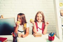 Le bambine mangiano la mela all'intervallo di pranzo Di nuovo all'istruzione domestica e dello scuola Amicizia di piccole sorelle fotografia stock libera da diritti
