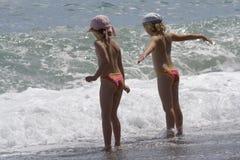 Le bambine si levano in piedi al mare durante la tempesta Immagini Stock Libere da Diritti