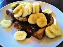 Le banane promuovono il pane inzuppato in latte/uova e zucchero e fritto in padella Immagini Stock