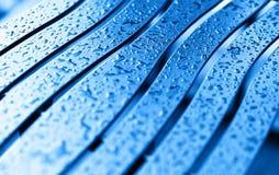 Le banc bleu diagonal avec la pluie laisse tomber le fond photographie stock