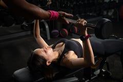 Le banc de aide de femme d'entraîneur personnel enfoncent le gymnase, s'exerçant avec le barbell image stock