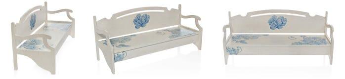 Le banc en bois a peint le blanc avec un modèle des fleurs bleues Photographie stock
