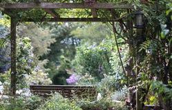 Le banc en bois sous l'auvent en bois, avec la vue sur le puits maintenu, a bien stocké le jardin reculé photo stock