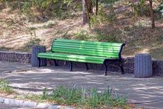 Le banc en bois vert avec des poubelles se tiennent sur l'asphalte en parc photographie stock libre de droits