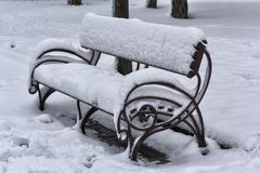 Le banc en parc est couvert dans la neige Image libre de droits