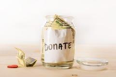 Le banconote del dollaro in barattolo di vetro con donano l'iscrizione ed il simbolo rosso del cuore Fotografie Stock
