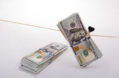 Le banconote del dollaro con un cuore tagliano su una corda Immagini Stock