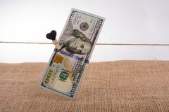 Le banconote del dollaro con un cuore tagliano su una corda Fotografie Stock