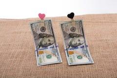 Le banconote del dollaro con un cuore tagliano su una corda Immagini Stock Libere da Diritti