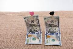 Le banconote del dollaro con un cuore tagliano su una corda Immagine Stock