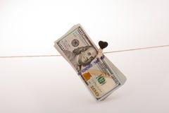 Le banconote del dollaro con un cuore tagliano su una corda Fotografie Stock Libere da Diritti