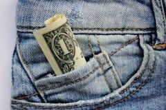 Le banconote in dollari 1 in blue jeans intascano, macro colpo fotografia stock libera da diritti