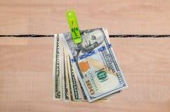 Le banconote in dollari differenti si asciugano su cavo Fotografie Stock