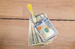Le banconote in dollari differenti si asciugano su cavo Immagine Stock