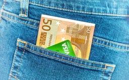 Le banconote 50 euro e visto della carta di credito in jeans posteriori intascano Immagini Stock