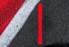 Le bande bianche rosse che segnano il fondo strutturato firmano e traccia di Fotografia Stock